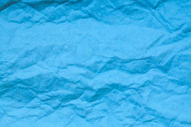 Fond de papier froissé bleu.