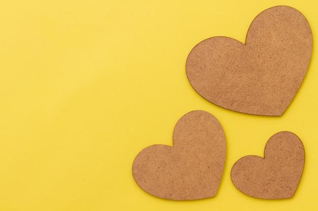 Fond de papier jaune avec trois coeurs en bois bruns.