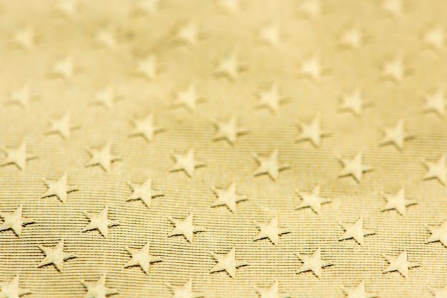 Fond de papier à motifs étoiles texturé or brillant