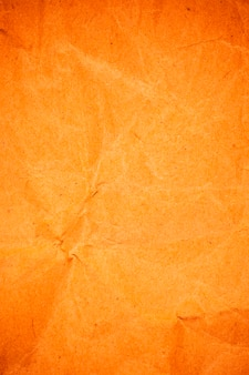 Fond de papier orange emballage froissé texturé.