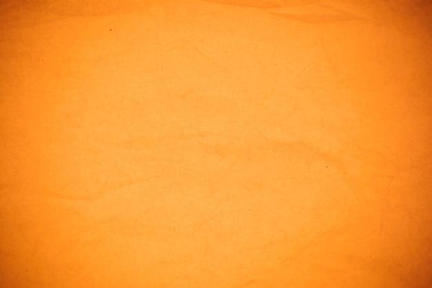 Fond de papier orange froissé.