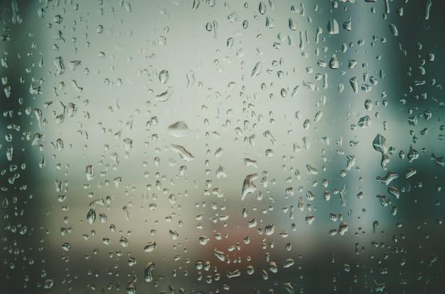 Fond et papier peint par gouttes de pluie et gouttes d'eau sur les vitres.