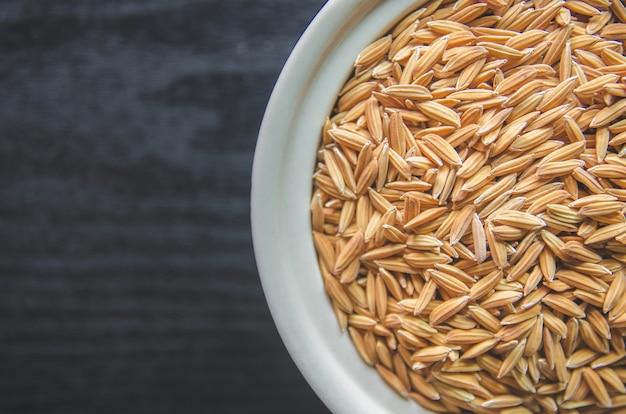 Fond et papier peint par tas de riz paddy et de graines de riz.