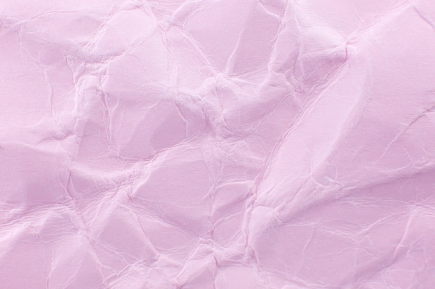 Fond de papier rose froissé. véritable macro texture battue. gros plan photo.