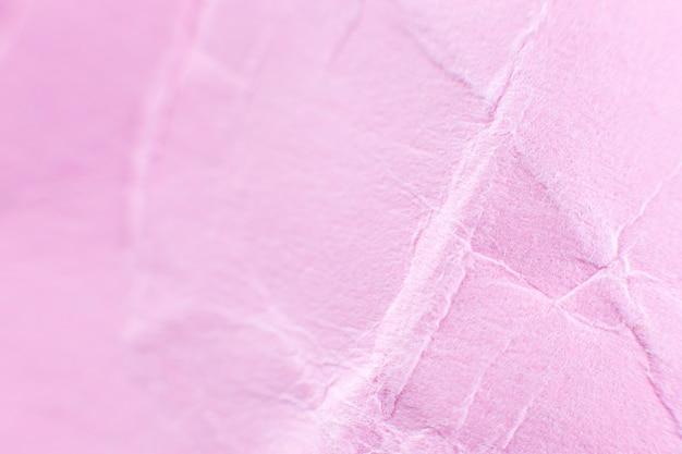 Fond de papier rose froissé. véritable texture macro battue. gros plan photo.
