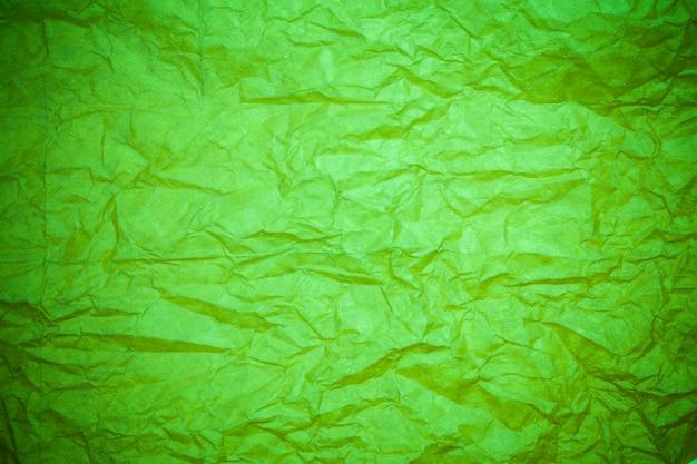 Fond de papier vert froissé.