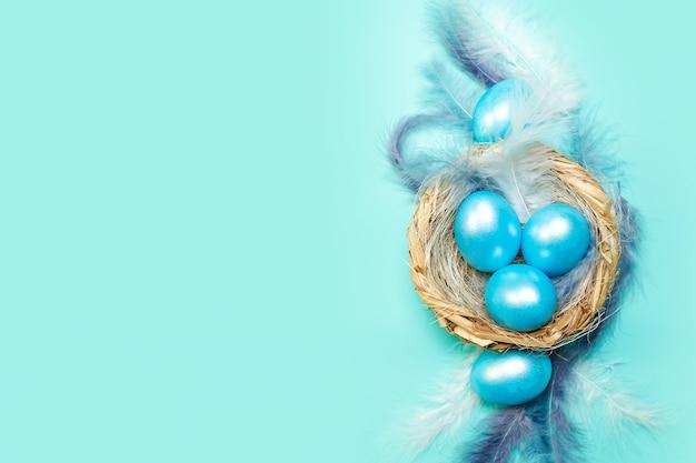 Fond de pâques bleu avec des oeufs colorés dans le nid avec des plumes