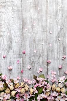 Fond de pâques festif de fleurs de pommier rose et pétales et oeufs de caille sur fond en bois peint en blanc.