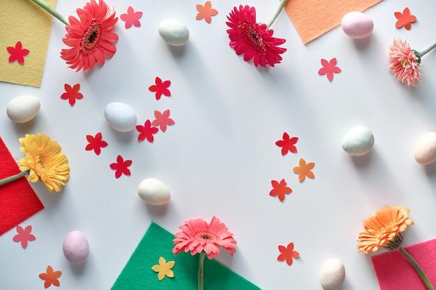 Fond de pâques avec des gerberas, des œufs sucrés, des confettis de fleurs et du feutre coloré pour des projets d'artisanat.