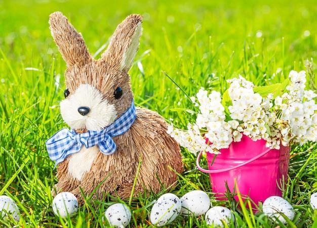 Fond de pâques avec lapin, oeufs, herbe verte et fleurs