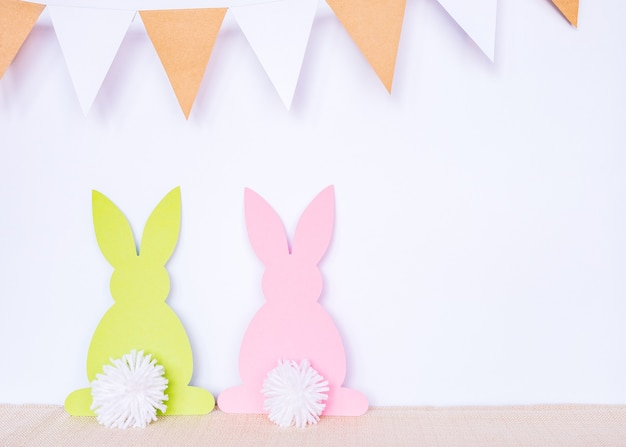 Fond de pâques avec des lapins en papier et des drapeaux de guirlande