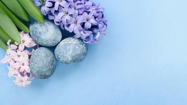 Fond de pâques avec des oeufs bleus et des fleurs de printemps. vue de dessus avec espace copie.