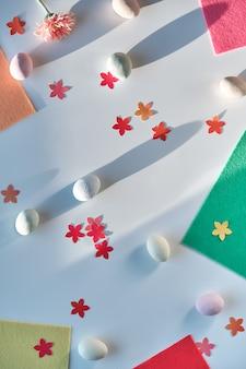 Fond de pâques avec des œufs, des confettis de fleurs et du feutre pour des projets d'artisanat. vue de dessus, longues ombres.