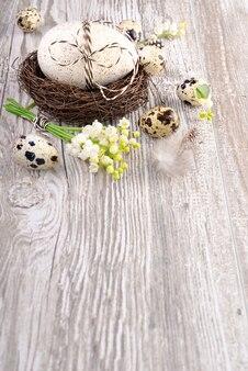 Fond de pâques avec des oeufs et des fleurs sur bois, espace de texte