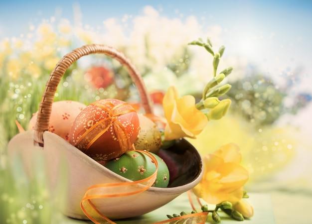 Fond de pâques avec des oeufs et des fleurs de printemps sur fond de printemps abstrait