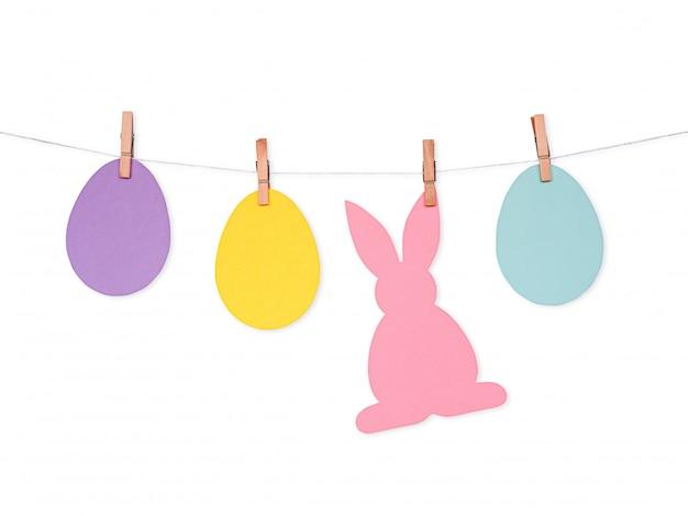 Fond de pâques avec des oeufs en papier coloré et le lapin sur corde