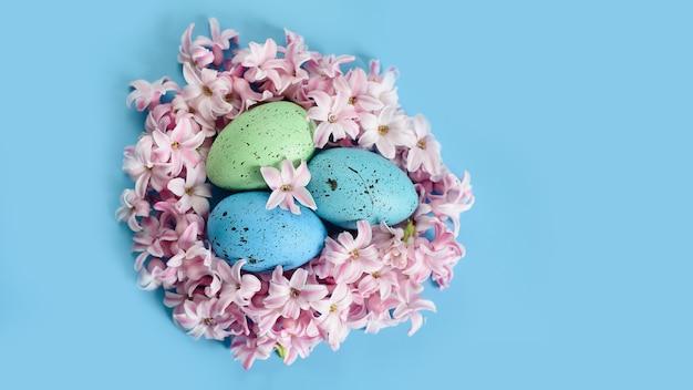 Fond de pâques avec des oeufs de pâques bleus dans le nid de fleurs de printemps. vue de dessus avec espace copie.