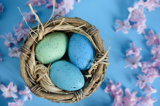 Fond de pâques avec des oeufs de pâques bleus dans un nid de fleurs de printemps