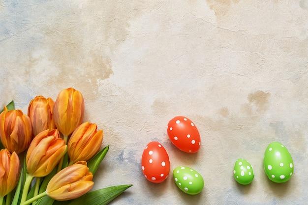 Fond de pâques. oeufs de pâques décoratifs et tulipes de printemps sur fond coloré. copier l'espace, haut
