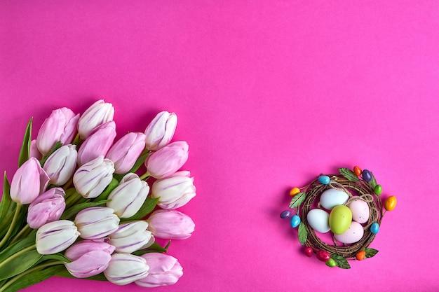 Fond de pâques. oeufs de pâques décoratifs et tulipes roses. carte de vacances. copiez l'espace, vue de dessus.