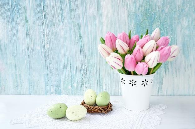 Fond de pâques. oeufs de pâques décoratifs et tulipes roses dans un vase blanc.