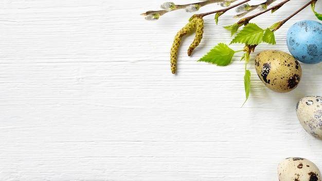 Fond de pâques avec des oeufs de pâques et des fleurs de printemps sur fond de bois blanc. vue de dessus avec espace de copie.