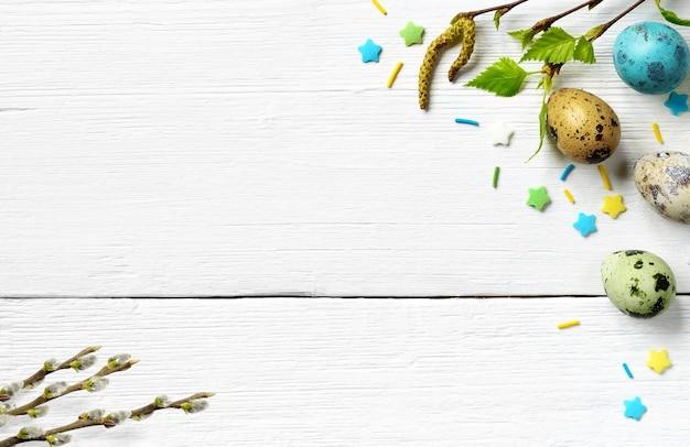 Fond de pâques avec des oeufs de pâques, saule et fleurs de printemps avec des feuilles vertes fraîches sur une table rustique en bois blanc. vue de dessus avec espace de copie.