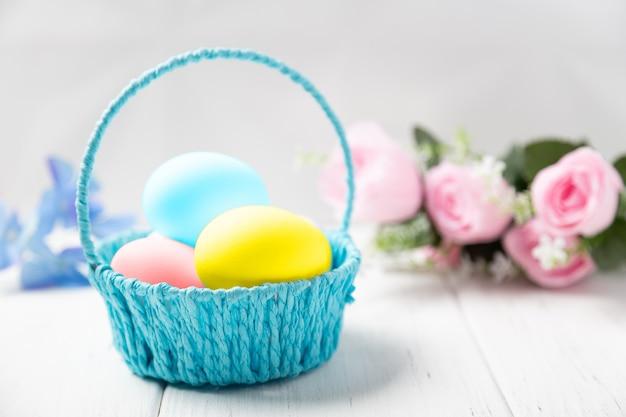 Fond de pâques. panier d'oeufs colorés sur une table en bois avec des fleurs de printemps