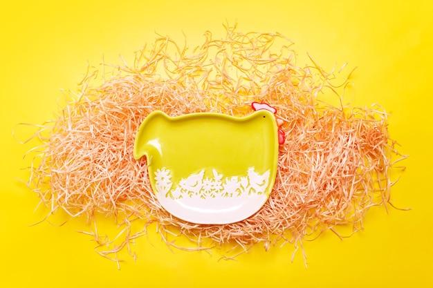 Fond De Pâques Avec Plaque De Poule Verte Sur Le Foin Sur La Couleur Jaune, Mise à Plat Photo Premium