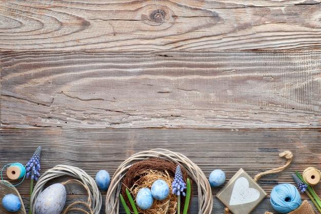 Fond de pâques rustique avec des oeufs, des fleurs de jacinthe bleues et un coeur en bois