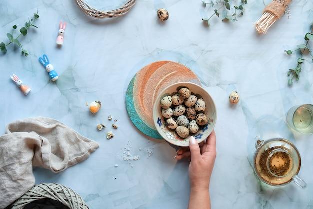 Fond de pâques zéro déchet sur table en marbre. oeufs de pâques de caille et décorations printanières naturelles et brindilles d'eucalyptus.