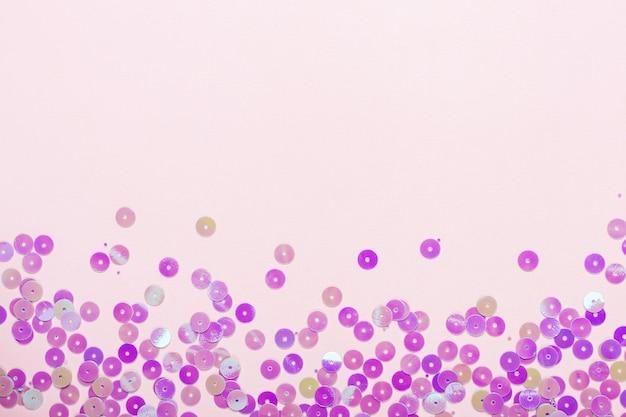 Fond pastel festif avec des confettis holographiques scintillants.