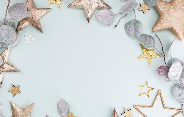 Fond pastel festif. étoiles de noël et paillettes brillantes, confettis sur fond pastel. fond de noël, mise à plat.