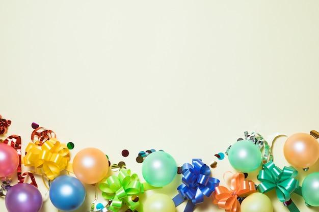Fond pastel lumineux de fête d'anniversaire avec des banderoles, des confettis, des ballons sur le fond jaune.