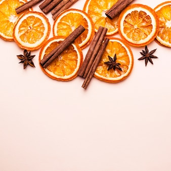 Fond pastel rose de noël des tranches d'orange sèche et bâtons de cannelle