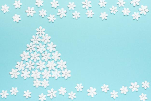 Fond pastel de vacances, flocons de neige blancs et arbre de noël sur fond bleu doux, mise à plat, vue de dessus