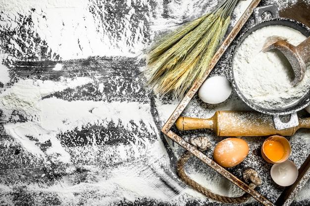Fond de pâte farine aux œufs et rouleau à pâtisserie sur la table en pierre