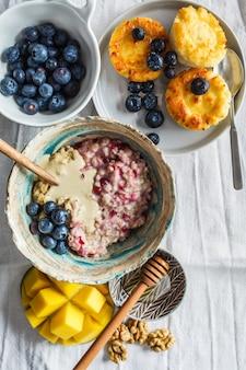 Fond de petit déjeuner. gruau, crêpes au fromage cottage avec des baies et des fruits sur fond sombre.