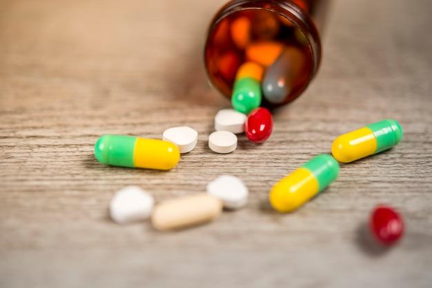 Fond de pilule sur une table en bois qui débordent de la bouteille de pilules.
