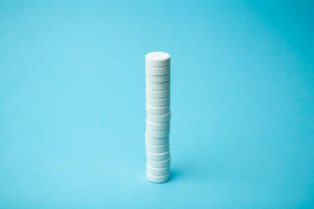Fond de pilules. pilules, traînées et concept de médecine. comprimés blancs sur fond bleu