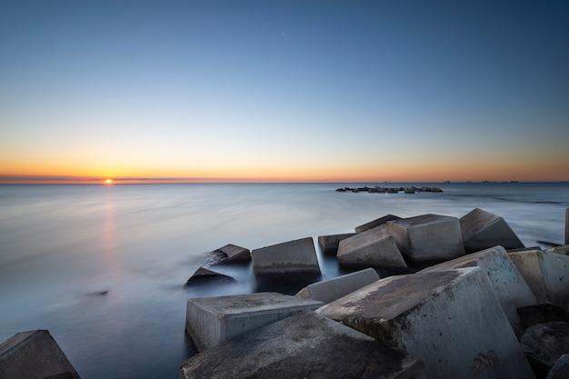 Fond de plage au lever du soleil avec des roches d'un brise-lames