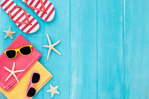 Fond de plage de bronzage d'été, lunettes de soleil, tongs, espace copie sur fond en bois bleu