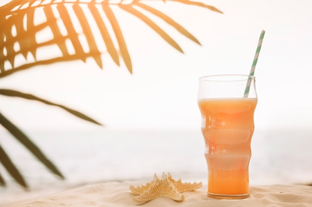 Fond de plage avec cocktail et feuille de palmier