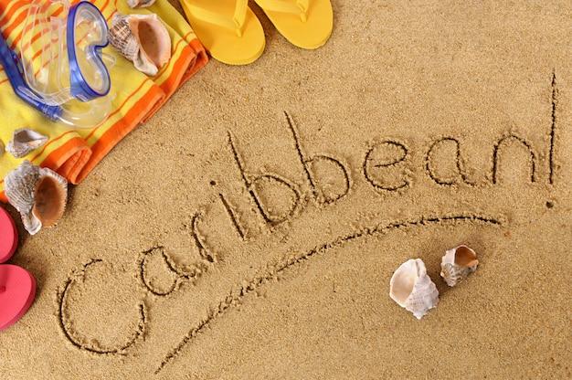 Fond de plage avec une serviette et des tongs et le mot caraïbes écrit en sable