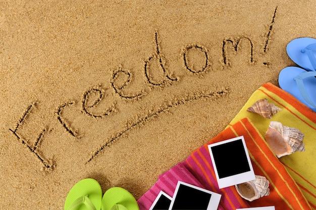 Fond de plage avec une serviette, des tongs, des photos vierges et le mot freedom! écrit dans le sable