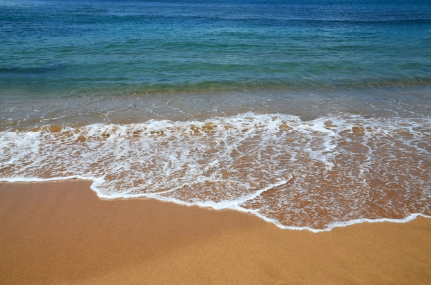 Fond de plage tropicale avec de l'eau bleue de l'océan avec des vagues et du sable jaune. paysage marin abstrait. concept de vacances d'été.