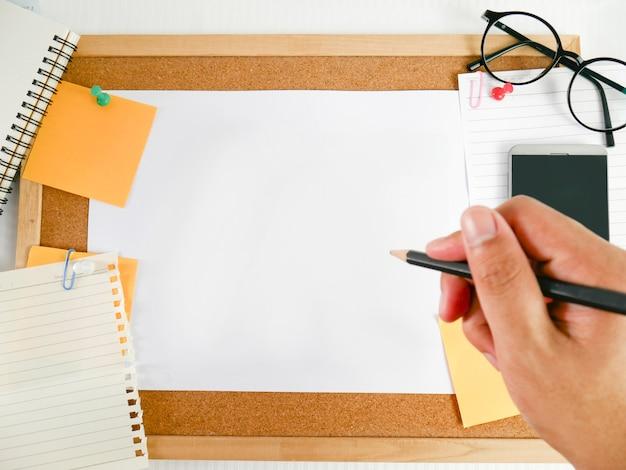 Fond d'une planche de bois, papier à lettres, papier vierge avec du matériel, tels que des crayons, des lunettes, de l'argent, des téléphones portables et des calendriers,