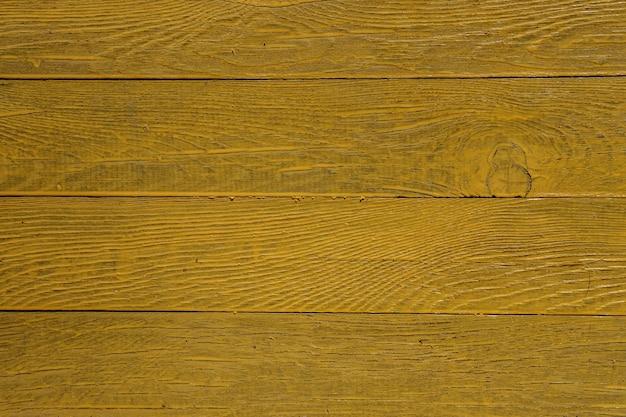 Fond de planches naturelles clouées horizontalement et peintes avec de la peinture jaune vif.