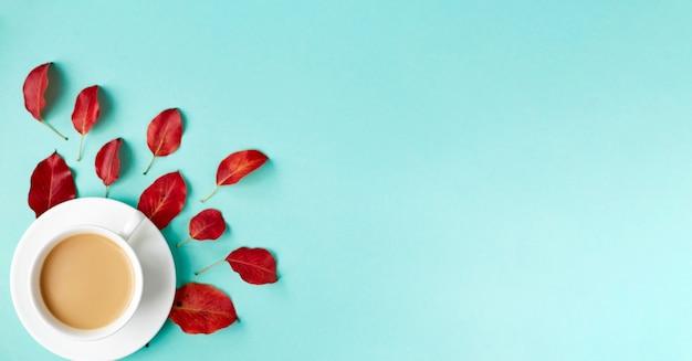 Fond plat d'automne sur bleu. composition avec des feuilles rouges réalistes et une tasse de café. bonjour concept d'octobre. espace de copie