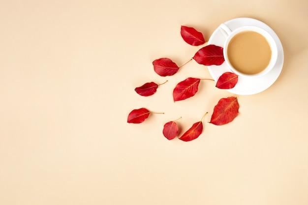 Fond plat d'automne sur jaune. composition avec des feuilles rouges réalistes et une tasse de café. bonjour concept d'octobre